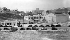 The sound stage and Animator's Building #1 at the original Walt Disney Studio, located at 2719 Hyperion Avenue, taken toward the southwest from across Monon Street, courtesy of David Lesjak (1931). John Marshall High School is visible on a low hill in the distance. A Gelson's Market occupies the site today.