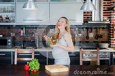 The smiling pregnant woman in kitchen is eating vegetable salad. Healthy food.