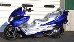 Blue custom scooter with flames (I believe it's a Suzuki Skywave)