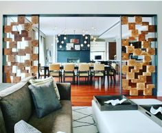 Beautiful room divider made using raw wooden logs and placed them abstractly with each other .The main attractive element of the space.Mainly its is diving the dining space and living rooms . Sofa units with cushions and designer center table . Big wooden dining table placed along with wooden chairs having leather finish appearance .Above ceiling with lovely hanging element .