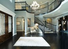 Elegant foyer with spiral staircase welcomes friends and family