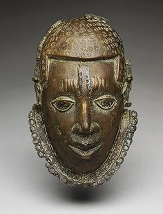 """""""Pectoral Ornament: Face, 15th–17th century. Cast brass masks such as this one were owned by paramount chiefs and titleholders of the Benin kingdom. Representing the face of the oba himself, these masks were worn suspended from the neck to indicate rank and demonstrate fealty to the king. As Benin expanded its political influence and military control over many of its neighbors, those foreign rulers who were absorbed into its political system also received these masks."""""""