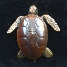 """This sweet creature has legs and a head that move, and garnet eyes. Bob's turtles are nearly 2"""" long and are a joy to hold. Bronze, sterling and shibuichi Designed and produced by Robert Burkett."""