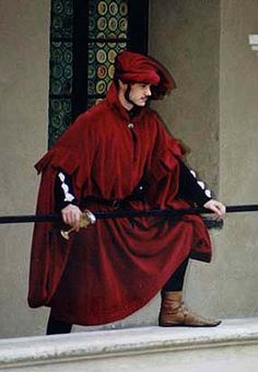 """Red robe        Men's robe with """"sack sleeve"""" made of red velvet, doublet and hoses. Chaperon is twisted hood. About 1410"""