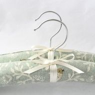 Covered in a bird print fabric, these handmade padded coat hangers are both pretty and practical. The cotton fabric has a mint coloured background and small brown birds on cream branches. An ivory satin ribbon and bow provide the finishing touch. The ...