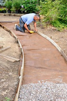 This image shows the process of crafting a stone walkway, with the builder laying down wood frame.