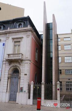 A modern lift, next to a 20th-century building on Avenida da Liberdade. The red box is a Lisbon's typical street mailbox.