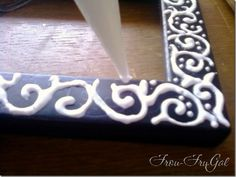 Dress up a cheap frame by decorating is with glue, let it dry, and then paint over it with one solid color and it looks like a specialty carved frame!