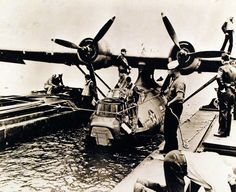 PBY alongside barges for refueling and rearming, August 11 1943. Official U.S. Navy photograph, now in the collections of the National Archives.