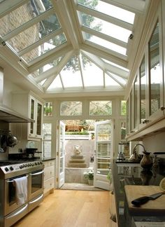 A galley kitchen with a greenhouse feel.  This kitchen really brings the outside in between the skylights in the roof and the doors opening out onto a charming patio.