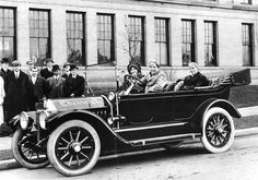 """The first Chevrolet automobile produced in Detroit, 1912. Louis Chevrolet, standing w/o hat. W.C. Durant, standing,  with derby hat at the right end of the group. Cliff Durant (W.C.'s son) at the wheel, his wife in the passenger seat. Folder """"Photographs, Automobiles and related."""" Box 15, Frank Angelo papers."""