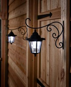 """The Set of 2 Solar Lanterns with Hanging Brackets adds a soft glow to your porch or entryway. You can also place it on a fence to illuminate your backyard. Each light is easy to hang with the included hardware and gives off a cool, white light. 9-1/2""""W x 4-3/8""""D x 8-3/4""""H with bracket, each. Metal, polypropylene and plastic. No wires. You get 2 Ready to ship by 05/26/2018 Details: 9-1/2""""W x 4-3/8""""D x 8-3/4""""H with bracket, each Metal, polypropylene and plastic Solar powered"""