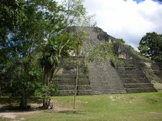 Pyramid of the Lost World, astronomical observatory originally had masks of night & day jaguar/sun god K'inich Ahau. First version built 500 bc. Mundo Perdido complex was rebuilt many times over the course of its history. By  250–300 its architectural style was influenced by Teotihuacan in the Valley of Mexico, including the use of talud-tablero form. In the Early Classic period (250–600) the Mundo Perdido became one of the twin foci of the city, the other being the North Acropolis.