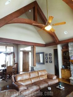 An arched king truss made with our Woodland fake beams nicely balances the living room vertically and works around the ceiling fan.