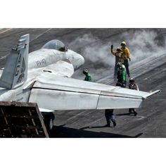 Flight deck crew position an FA-18E Super Hornet into launch position aboard USS Eisenhower Canvas Art - Giovanni CollaStocktrek Images (18 x 12)