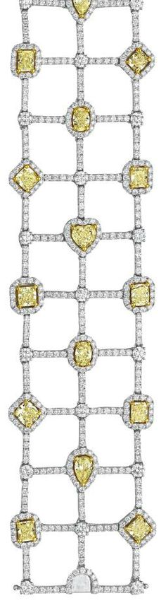 A Diamond and Yellow Diamond Bracelet. Of flexible design, the wide openwork band composed of three rows of vari-cut yellow diamonds, within a circular-cut diamond surround, interspaced with circular-cut diamond connector links, mounted in 18K white gold. Philips de Pury.