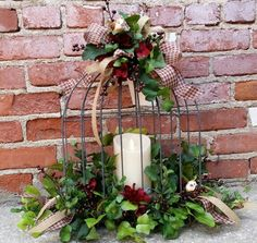 This wire birdcage is decorated with burgundy berries, ivy, checked burgundy ribbon and birds. I then added a fireless candle in the center . Design created by Twigs.