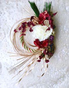 お正月を華やかなしめ縄飾りでお正月らしい色合いで大きさもあり艶やかなしめ縄飾りです。花材:プリザーブドフラワーの松・アーティフィシャルフラワーのピオニー・薔薇・マム・オンシジューム・デンファレ・紫陽花・ベリー・ドライフラワーの松かさ・カラマツ・蓮の実・水引・西陣織リボンなど※再販時には少し花材の変更や形の違いなどもございますので宜しくお願い申し上げます。また画像も変わりますのでご了承いただけたら幸いでございます。サイズ 約46cm×33cm×10cm