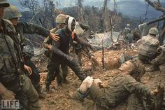 """Reaching Out: Photo by Larry Burrows, 1966      Marine Gunnery Sgt. Jeremiah Purdie (left), wounded in a firefight during """"Operation Prairie"""" in Vietnam, reaches out to a stricken comrade in Larry Burrows' astonishing 1966 photograph. Here, in what might be the greatest picture from a legendary career, Burrows captured for LIFE magazine's millions of readers both unfathomable desolation and galvanic camaraderie in the utterly alien universe of Southeast Asia. That the image, made at the very…"""