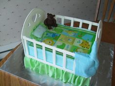 Baby Crib - A 11x15 cake cut in half and stacked. Gumpast rails, teddy bear and blanket. The blanket on top of the mattress is an edible image. Fondant ruffles.
