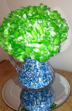 Sprinkle baby shower flower arrangement for food buffet. We simply slipped a glass with flowers (green hydrangeas) into the pitcher and filled the pitcher up to the glass level with sprinkles that matched shower colors.