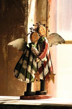 striped hugging wooden angels with curly wire hair and metal wings and stars
