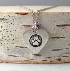 This is a teeny, sweet embossed paw print of your 'actual' dogs paw print. Keep your pup close to you in this wee heart shaped piece. This design is also available with your child's handprints.