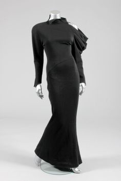 Claude Montana black jersey evening gown, 1980s, with one rounded curving shoulder and sleeve, the other with exposed shoulder and draped pleats, curving waist seam, long narrow skirt that slightly flares at the hem
