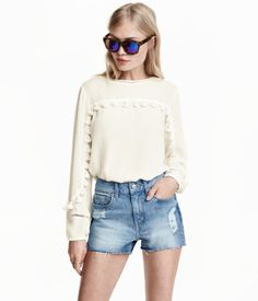 Short, 5-pocket shorts in washed denim with heavily distressed details, a high waist, and raw-edge hems.