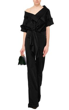 This **Johanna Ortiz** jumpsuit is rendered in cotton and features a v-neck, off-the-shoulder short sleeves with ruffle trim, a relaxed bodice with a self-tie waist, and a wide leg pant.