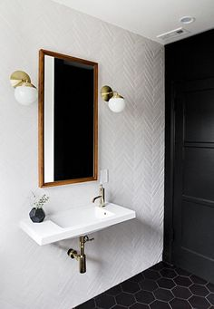 A black door painted Farrow & Ball Pitch Black opens to a black and white bathroom featuring walls clad in a white herringbone tiles. Lined with a West Elm Floating Wood Wall Mirror illuminated by Cedar Moss Alto Sconces over a white porcelain wall-mount sink, alongside a black hex tiled floor.
