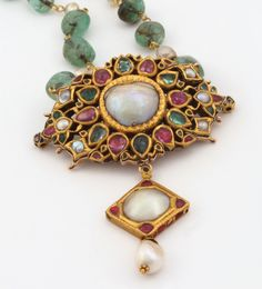This pendant is set with two large pearls, accented with rubies and emeralds, and suspends a single drop-shaped pearl. Originally created as an amulet or 'bajuband', it was later reconstructed and strung as a pendant with a beautiful chain of emerald beads and pearls.