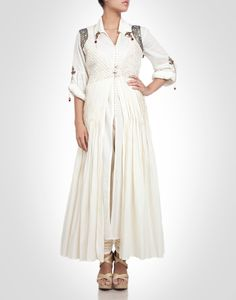 White suit embellished with metallic embroidery and metal brooches. Shop Now: www.kimaya.in