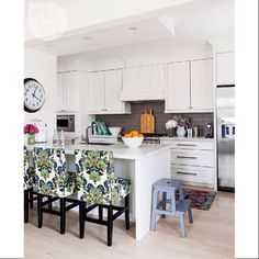 Shaker-style #cabinetry provides textural interest in this mostly white #kitchen, which also features a dark-tiled #backsplash + patterned stool slipcovers. LIKE? {Photo: Donna Griffith, Design: Julia Grieve @prelovedjules + Susan Shaw @susan4000} #kitchendesign #homedecor #interiordesign