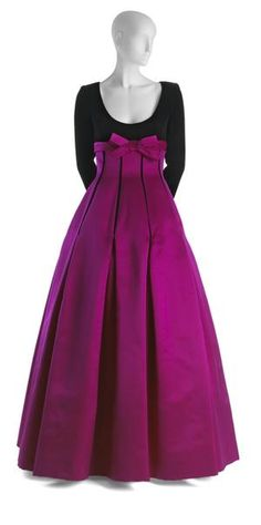 Oscar de la Renta Evening Gown, 1992  -Evening dress of black velvet and fuchsia satin. The dress has an empire-length bodice of black velvet, with a scoop neckline and long fitted sleeves which have hidden zipper closures. -The Empire waistline is accented with a horizontal band of fuchsia satin with bow at center front.