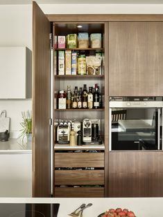 Slim kitchen pantry cabinet design in American Black Walnut with built-in lighting, countertop and handleless drawer storage.