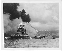Photograph of the capsized USS Oklahoma BB-37 and a slightly damaged USS Maryland BB-46, 12/07/1941