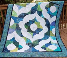 This handmade twin size quilt brings refreshing blues and greens into your bedroom in an elegant ogee arch design. It features machine-pieced curves in blue, aqua and green batik fabrics. The background and backing fabric is a pale grey print of tiny leaves. It is quilted by machine in an ogee medallion design that includes spirals, feathers and parall...
