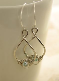 Pear shape silver earrings with herringbone wrapped luster aquamarine color lampwork glass. , via Etsy.