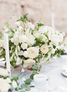 Elegant, low gold compote vases spilling with nagi foliage, fresh rosemary, olive, ivory vendela roses, white sweet peas and ivory spray roses. Surrounded by cut glass and mixed gold mercury glass votives.