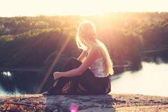 Blonde woman enjoying the sunset view near river