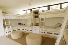 Kids' bunk room features U shaped built-in bunk beds accented with ladders as well as round cheetah ottomans.