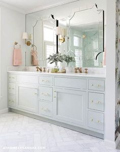 A white marble herringbone tile floor leads to a stunning bathroom boasts a pale…