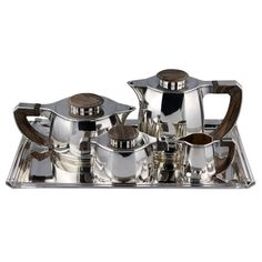 ean Puiforcat's genius was to attain a radical evolution in his work while creating a synthesis of the totality of his experience. Designed in 1925, this Silver Tea and Coffee service in cut-off corner design. Handles and cover nobs in Brazilian Rosewood. There is no tray with this set.