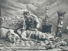 """In many societies, healers or shamans function as intermediaries between the physical and spiritual world. Illness is thought to be caused by a loss of the soul from the body and the shaman's role is enter that world and retrieve it so body and soul are whole again. The use of """"spirit guides"""", powerful plants or totemic animals assists the shaman in the spirit world. This image from 1906 is of a Tlingit Healer. Photo credit: National Anthropological Archives."""