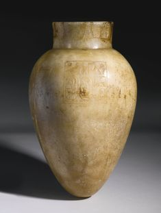 "An Egyptian Alabaster Jar, 18th Dynasty, reign of Amenhotep III, 1390-1353 B.C., with tapering ovoid body and fragmentary slightly flaring neck, the shoulder carved with a square panel containing the nomen and prenomen of Amenhotep III, and ""Lord of the Sed Festival,"" the inscription perhaps later. Height 13 1/2 in. 34.3 cm."