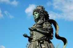 Estátua da Rainha D. Catarina de Bragança (Lisboa) - Distrito de Lisboa | Guia da Cidade | Região de Lisboa - A estátua da Rainha D. Catarina de Bragança no Parque Tejo, é um réplica de outra construída nos EUA pela Associação Friends of Queen Catherine, de autoria da pintora e escultora Audrey Flack, nascida em Nova Iorque em 1931. A estátua é de bronze e tem cerca de 10 metros.