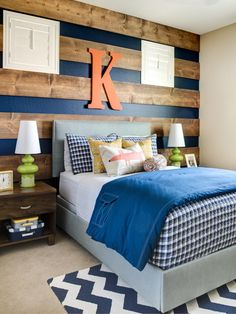 Wood boards stripe the navy accent wall in this boy's bedroom, creating depth and texture behind the gray upholstered headboard. Layers of decorative pillows cushion and decorate the bed, which boasts a blue blanket with a cargo pocket. Contemporary green table lamps and a monogram letter add pops of color.