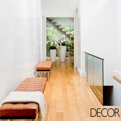 A predominância do branco destaca o acabamento em madeira no piso e o revestimento em couro dos bancos que compõem com elegância o corredor