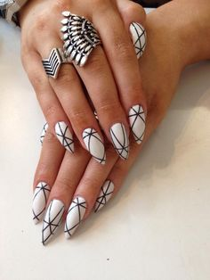 Stiletto white nails with geometrical black lines.